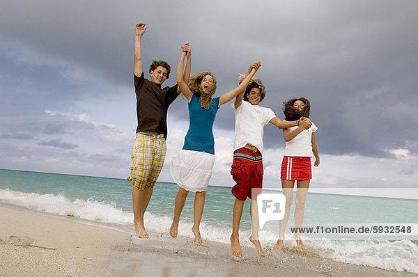 Jugendlicher  Strand  Junge - Person  springen  2  Mädchen