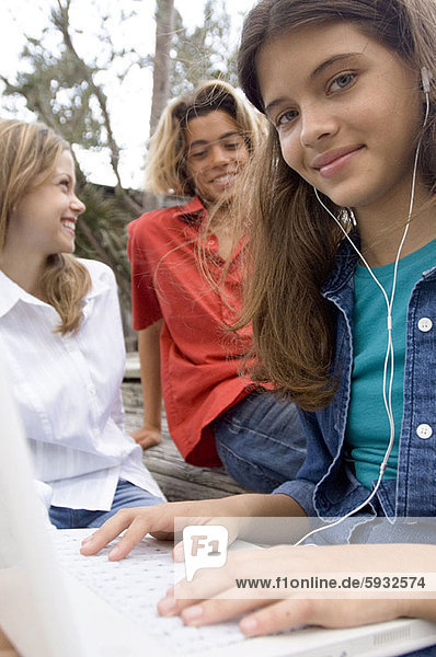 Portrait of a teenage girl using a laptop with her two friends sitting beside her. Portrait of a teenage girl using a laptop with her two friends sitting beside her