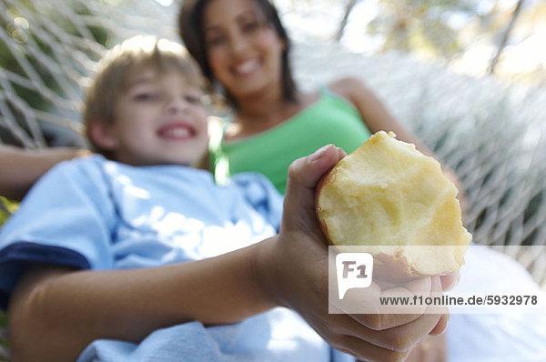 liegend  liegen  liegt  liegendes  liegender  liegende  daliegen  Junge - Person  halten  Hängematte  Close-up  close-ups  close up  close ups  Apfel  Mutter - Mensch