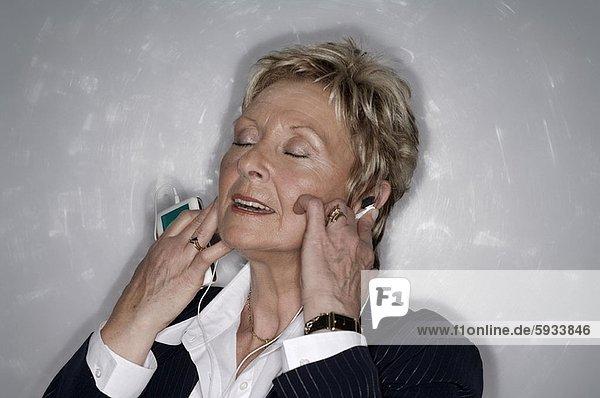 Senior  Senioren  Frau  zuhören  Spiel  Close-up  close-ups  close up  close ups  MP3-Player  MP3 Spieler  MP3 Player  MP3-Spieler