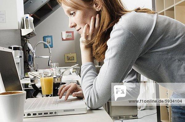 Profil  Profile  benutzen  Frau  Notebook  Küche  jung  Seitenansicht