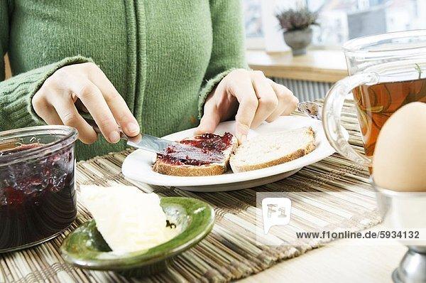 Anschnitt  eincremen  verteilen  Frau  Brot  Mittelpunkt  Ansicht  auftragen  Marmelade