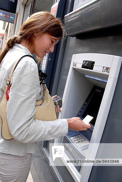 20 Jahre alte Frau  die Bargeld an einem Geldautomat abhebt