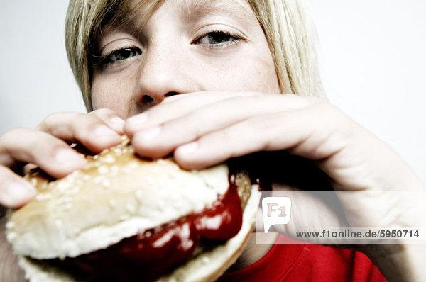 Close-up of a boy biting a burger. Close-up of a boy biting a burger