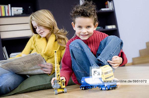 hinter Portrait Junge - Person Spielzeug Mutter - Mensch Zeitung spielen vorlesen