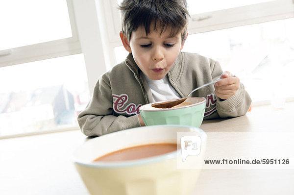 sitzend  Junge - Person  am Tisch essen  trinken  Tisch  Suppe