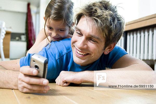 Handy liegend liegen liegt liegendes liegender liegende daliegen benutzen Menschlicher Vater Kurznachricht Tochter