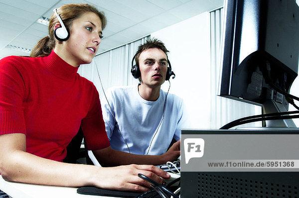 sitzend  nebeneinander  neben  Seite an Seite  benutzen  Jugendlicher  Computer  Junge - Person  Kopfhörer  Kleidung  Mädchen