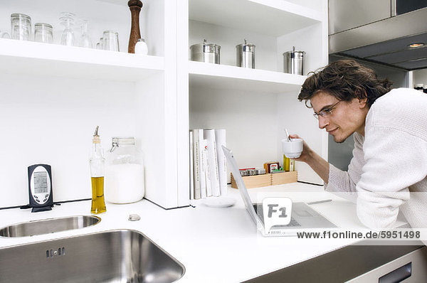 Profil  Profile  angelehnt  benutzen  Mann  Notebook  Küche  jung  Seitenansicht  Tresen