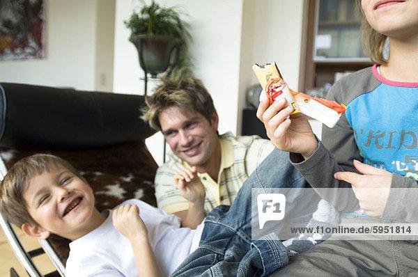 sitzend  Bruder  Menschlicher Vater  Schwester  halten  Eiscreme  Eis