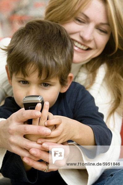 Handy  sitzend  Sohn  halten  Close-up  close-ups  close up  close ups  auf dem Schoß sitzen  Kurznachricht