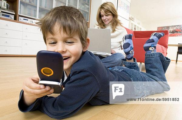 Handy hinter benutzen Notebook Junge - Person halten Kurznachricht Mutter - Mensch
