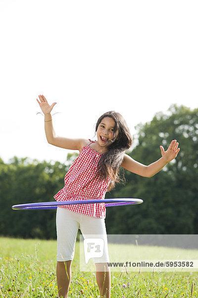 Mädchen mit einem Hula-Hoop auf einer Wiese