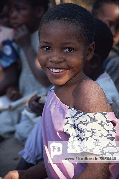 Head and shoulders portrait of girl  smiling and looking at the camera  Mozambique  Africa