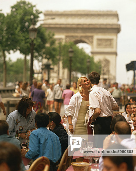 Greeting friends at an outdoor cafe on the Champs Elysees with the Arc de Triomphe behind  Paris  France  Europe