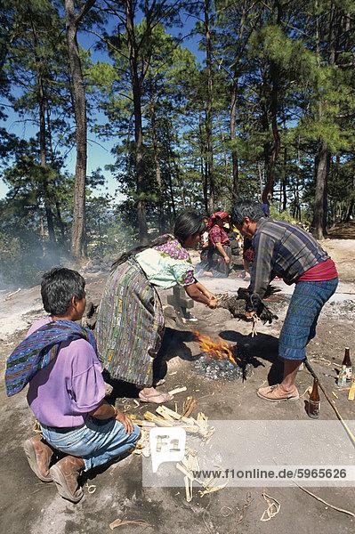 Mann und Frau Opfern ein Huhn über einem Feuer während der heidnischen Anbetung an Pascual Abaj  Chichicastenango  Guatemala  Zentralamerika