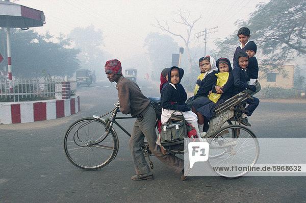 Schulkinder fahren in einer Rikscha in Agra  Uttar Pradesh  Indien  Asien