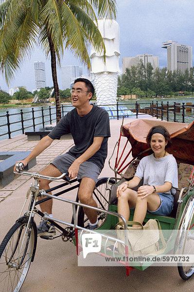 Tourist in eine Trishaw am Merlion-Denkmal in Singapur  Südostasien  Asien
