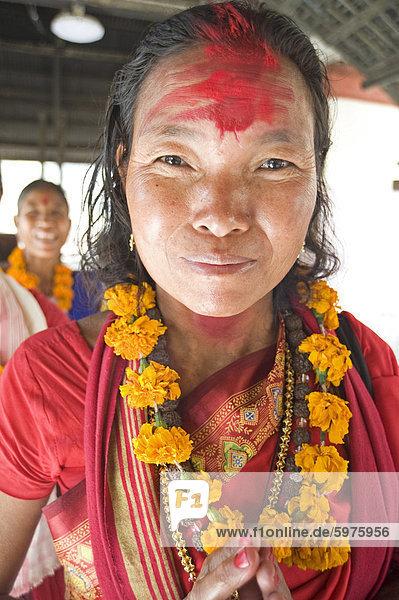 Frau aus Sonapur  östlich von Guwahati  der Shakti (Sun Worship) Sekte  traditionell in rot gekleidet garlanded mit Tempel rot auf Stirn  Kamakhyal Tempel  Guwahati  Assam  Indien  Asien