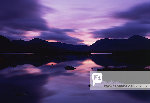Reflections in the lake of sunset over dark hills of Rannoch Moor in the Highland region of Scotland  United Kingdom  Europe