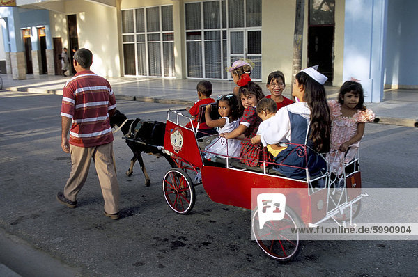 Ziege Karre mit Kindern an einem Sonntag in der Plaza De La Revolucion  Bayamo  Kuba  Westindische Inseln  Mittelamerika