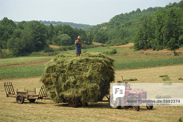 Landwirtschaft-Paar mit Traktor und volle Anhänger während der Heuernte in einem Feld nahe Lalbenque  Lot  Midi-Pyrenees  Frankreich  Europa
