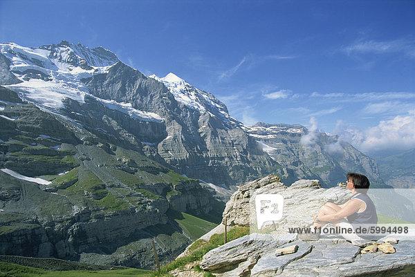 Walker auf einem Felsen  Blick auf den Gipfel der Jungfrau  13642ft  im Berner Oberland  Schweiz  Europa