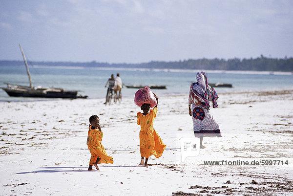 Junge Mädchen und ihre Mutter zu Fuß entlang dem Strand  Sansibar  Tansania  Ostafrika  Afrika