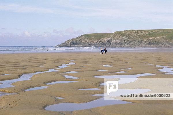 Surfers walking on beach  Holywell Bay  Cornwall  England  United Kingdom  Europe