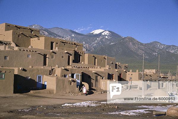 Lady fegt  nachdem Besucher haben abreiste  mehrstöckige Adobe-Gebäude im Norden Komplex aus um 1450 N.  Taos Pueblo  UNESCO Weltkulturerbe  Taos  New Mexico  Vereinigte Staaten von Amerika (U.S.A.)  Nordamerika