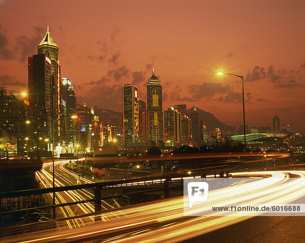 Lights on skyscrapers and traffic trails in the financial district of Hong Kong at sunset  China  Asia