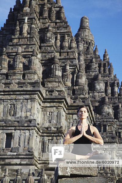 Woman performing yoga  Prambanan complex  UNESCO World Heritage Site  Java  Indonesia  Southeast Asia  Asia