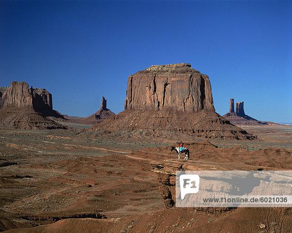 Eine Frau auf dem Pferderücken in der Wüste mit Felsformationen verursacht durch Erosion in den Hintergrund  im Monument Valley  Arizona  Vereinigte Staaten von Amerika  Nordamerika