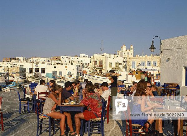 Touristen Essen und trinken außerhalb in einer Taverne in der Stadt Naoussa auf Paros  Kykladen  griechische Inseln  Griechenland  Europa