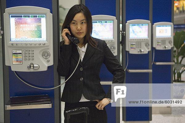 Eine chinesische Business-Frau anrufen Telefon am Beijing Capital Airport Teil des neuen Terminal 3 Gebäude eröffnete Februar 2008  zweite größte Gebäude der Welt  Beijing China  Asien