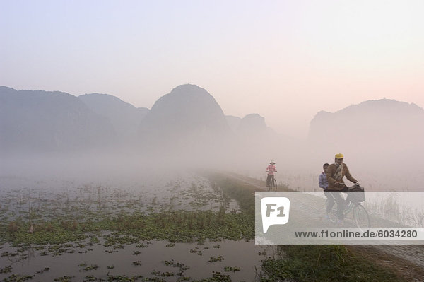 Bicycles in the morning mist at sunrise  limestone mountain scenery  Tam Coc  Ninh Binh  south of Hanoi  North Vietnam  Southeast Asia  Asia