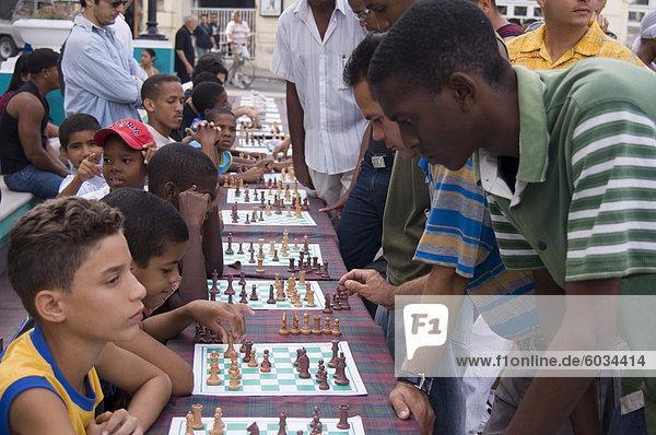 A group of school children competing in chess matches against adults  Parque Cespedes  Santiago de Cuba  Cuba  West Indies  Central America