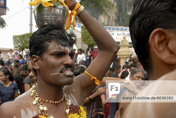Pilgrim known as kavadi (carrier) with pierced tongue  during the Hindu Thaipusam Festival  carrying container (paal kudam) of milk offerings from Sri Subramaniyar Swami Temple up to Batu Caves  Selangor  Malaysia  Southeast Asia  Asia
