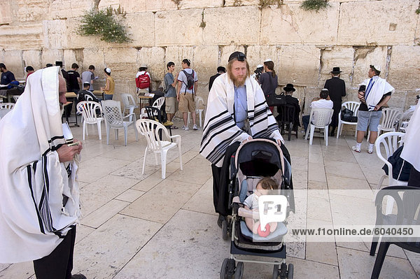 Jewish man with child in pram  praying at the Western Wailing Wall  Old Walled City  Jerusalem  Israel  Middle East
