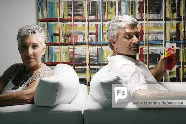 Zwei ältere Leute sitzen Rücken an Rücken