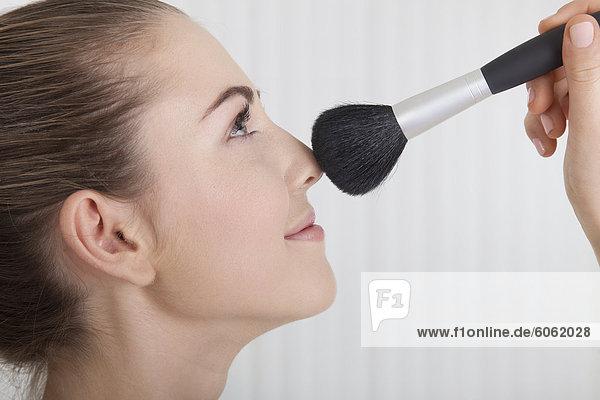 Junge Frau mit Kosmetikpinsel  Porträt