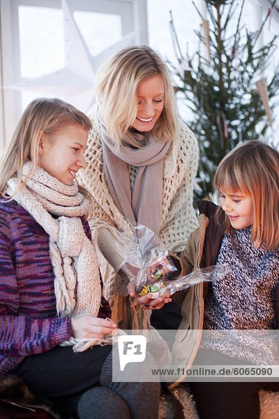 Woman giving Christmas present to girls in greenhouse