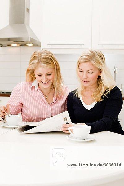 Zwei junge Frauen lesen Zeitung in Küche