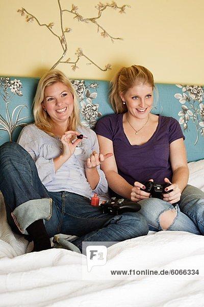 Zwei junge Frauen Video-Spiel im Schlafzimmer