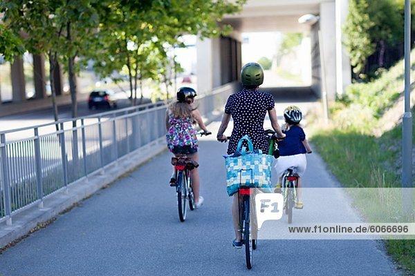 eine Frau und zwei Kinder Fahrräder