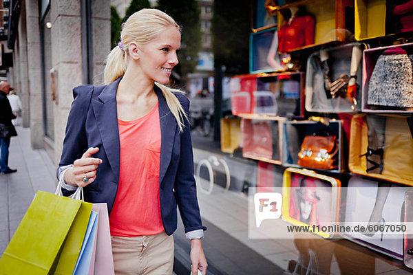 Frau mit Einkaufstüten Schaufensterbummel