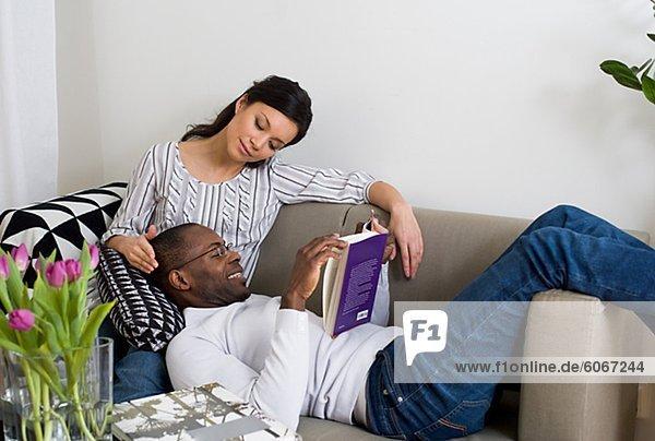 Paar auf Sofa  Man liest Buch