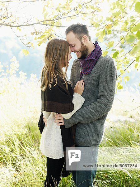 Young couple embracing under tree