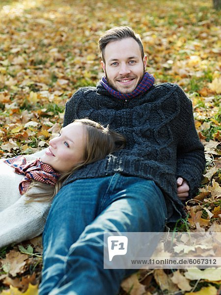 Portrait of young couple lying in leaves
