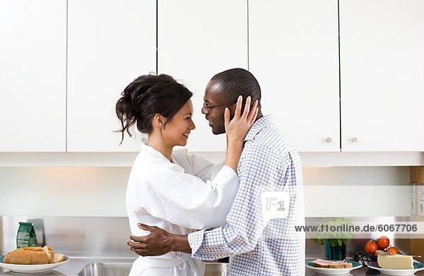 Paar umarmen in Küche am Morgen